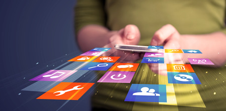 Woman holding smart phone with colorful application icons comming out