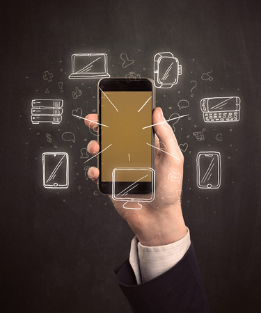 nas: Caucasian hand in business suit holding a smartphone with hand-drawn icons Stock Photo