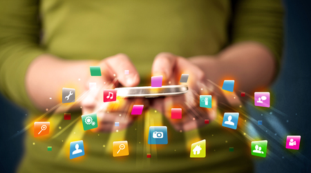 comming: Man holding smartphone with technology application icons comming out Stock Photo