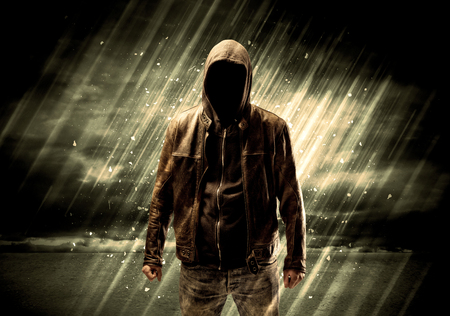 incognito: An incognito hooded stalker standing in the rain with his back in front of dark scary landscape concept