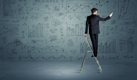 exponential: A businessman in modern stylish elegant suit standing on a small ladder and drawing pie and block charts on grey wall background with exponential progressing curves, lines, circles, angles, blocks, numbers Stock Photo