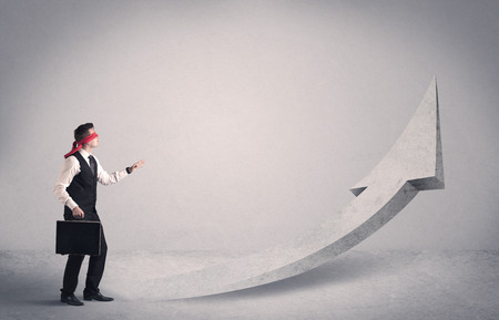 blindfolded: A scared blindfolded businessman forced to face a problem concept with illustrated arrow pointng to the sky in empty space. Stock Photo