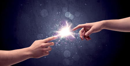 towards: Two male hands reaching towards each other, almost touching with fingers, lighting spark in galaxy background concept