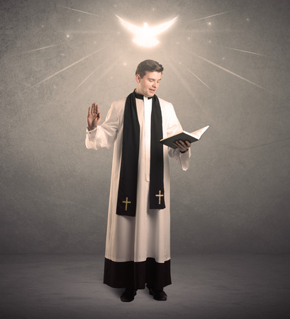 clergyman: A holy priest reading a prayer from the holy bible with illustrated glowing angel above his head concept. Stock Photo