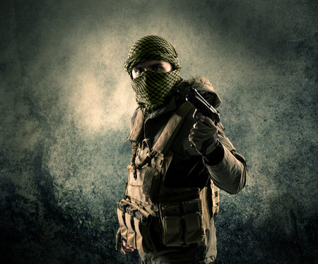 cyber terrorism: Portrait of a heavily armed masked soldier with grungy background concept