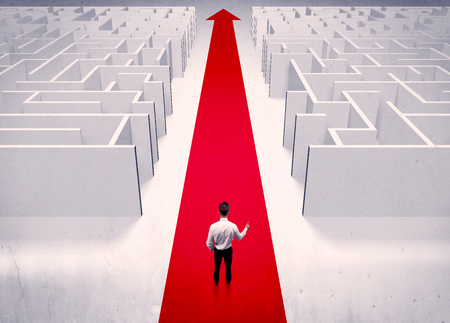 wayout: An adult elegant businessman standing on a red carpet arrow pointing ahead through a street with maze on two sides concept