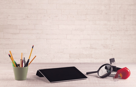pencils  clutter: Close up of business office desk with pen board coffee in front of empty white brick textured wall background.