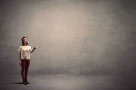 personal point of view: Caucasian woman standing in front of a blank grunge wall