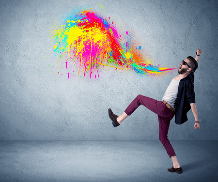 A funny hipster person in casual urban clothing shouting bright colorful paint on city wall concept Stock Photo
