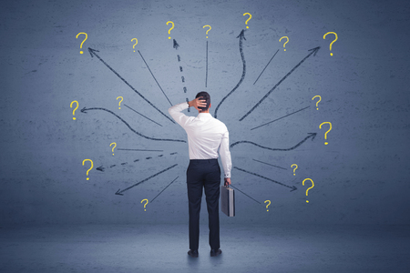 considerations: Businessman standing in front lines and question mark signs concept on background