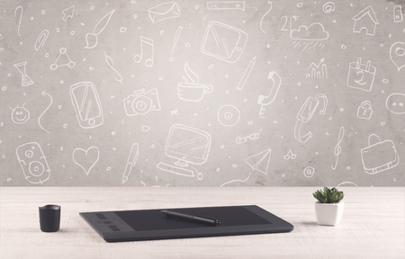pencils  clutter: Close up of business office desk with laptop tablet in front of brown wall background full of drawn communication icons and school items concept