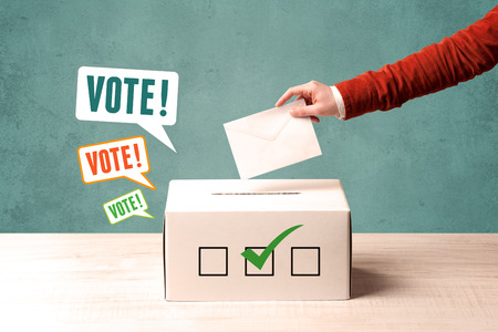 A hand placing a voting slip into a ballot box Stock Photo