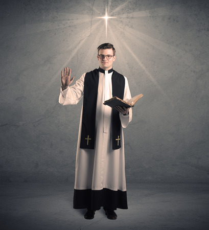 clergyman: A young male priest in black and white giving his blessing in front of grey wall with glowing cross concept. Stock Photo