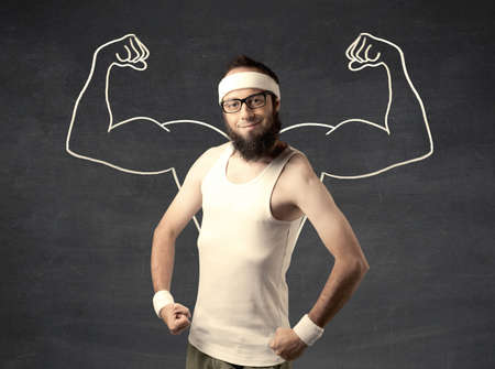 A young male with beard and glasses posing in front of grey background, thinking about lifting weight with big muscles, illustrated by white drawing concept. Stock Photo