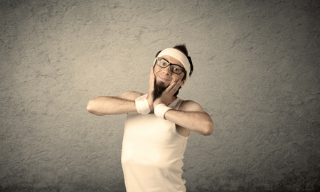 imagining: A young man with beard, headstrap and glasses posing in front of blank grey wall background, imagining he has big muscles