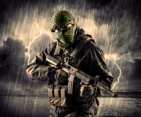 hijack: Portrait of a dangerous armed terrorist with mask and gun in a thunderstorm with lightning