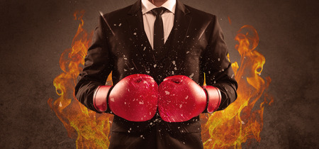 A strong sales person breaking something into pieces with red boxing gloves concept illustrated with glowing residue flying in the air. Stock Photo