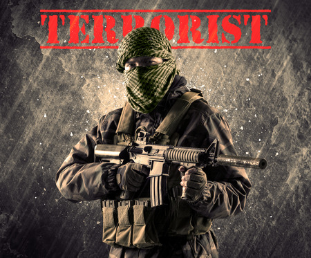 cyber terrorism: Portrait of dangerous masked and armed man with terrorist sign on grungy background