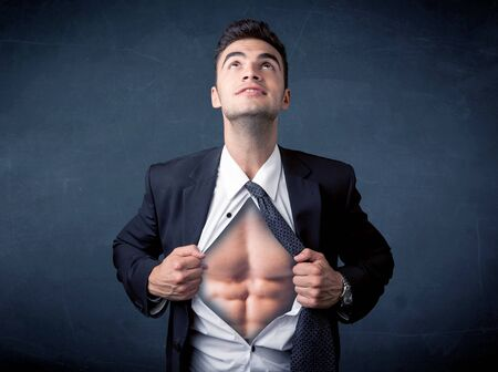 tearing: Businessman tearing off his shirt and showing mucular body concept on background