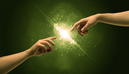 naked male: Two naked male hands about to touch, lighting the spark with modest explosion in front of green background concept