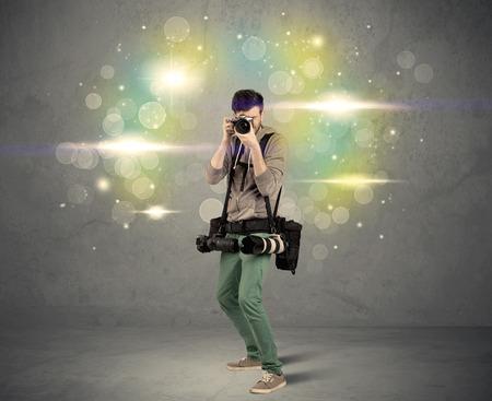 amateur: Un joven aficionado a la fotografía con el equipo de cámara profesional que toma el cuadro delante de la pared gris llena de colorido y brillante bokeh luces concepto