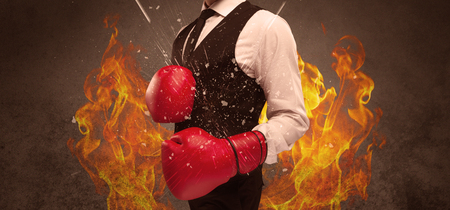 the residue: A strong sales person breaking something into pieces with red boxing gloves concept illustrated with glowing residue flying in the air. Stock Photo