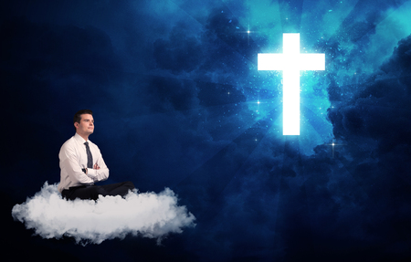 agnosticism: Caucasian businessman sitting on a white fluffy cloud looking and wondering at a big bright glowing cross