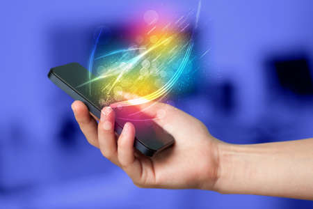 hand holding smart phone: Hand holding smart phone with abstract glowing lines concept