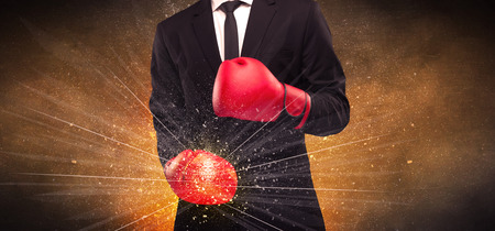 falling apart: A successful powerful business person in red boxing gloves concept with illustrated power lines and pieces falling apart in front of explosion. Stock Photo