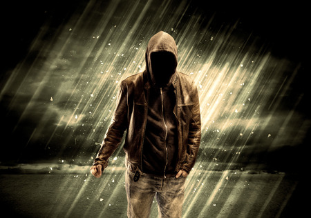 stalker: An incognito hooded stalker standing in the rain with his back in front of dark scary landscape concept