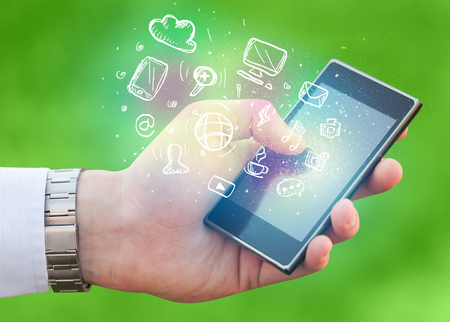 multimedia icons: Hand holding smartphone with glowing multimedia icons Stock Photo