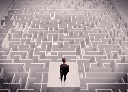 businessman thinking: A confused businessman thinking while standing on a square platform above a detailed maze