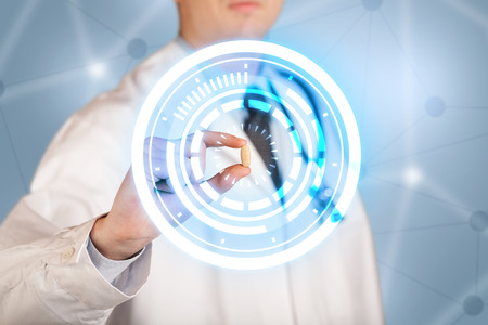A male  doctor in white coat showing a glowing pill in blue, white circles Stock Photo