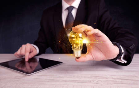 light worker: An elegant office worker holding a yellow sparkling light bulb in his hand while working in front of dark blue background concept.