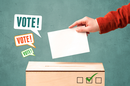 mail slot: A hand placing a voting slip into a ballot box Stock Photo