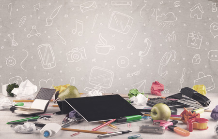 mess: Close up of business office desk with laptop tablet in front of brown wall background full of drawn communication icons and school items concept