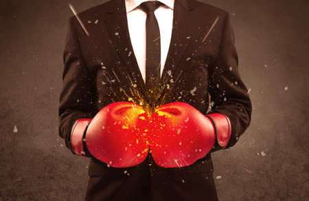 residue: A strong sales person breaking something into pieces with red boxing gloves concept illustrated with glowing residue flying in the air. Stock Photo
