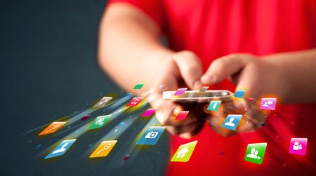 hubs: Man holding smartphone with technology application icons comming out Stock Photo