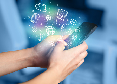 multimedia background: Hand holding smartphone with glowing multimedia icons Stock Photo