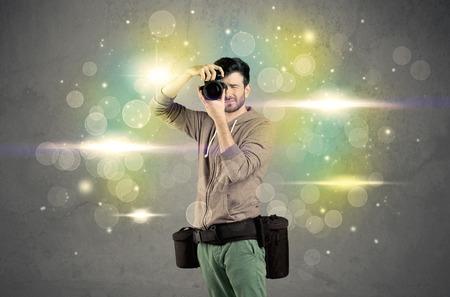 AFICIONADOS: Un joven aficionado a la fotografía con el equipo de cámara profesional que toma el cuadro delante de la pared gris llena de colorido y brillante bokeh luces concepto