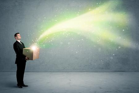 Heldergele, groene lichtstralen die aan een kartondoos ontsnappen die door jonge elegante mannelijke bedrijfspersoon in het modieuze kostuumconcept wordt gehouden. Stockfoto