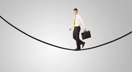A confident smiling salesman balancing on black wire in clear grey empty space concept Stock Photo