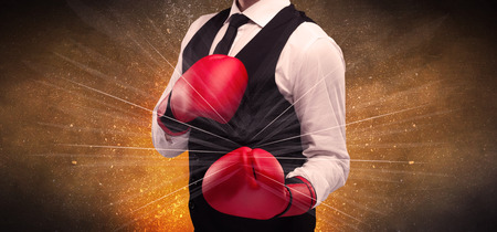 A successful powerful business person in red boxing gloves concept with illustrated power lines and pieces falling apart in front of explosion. Stock Photo