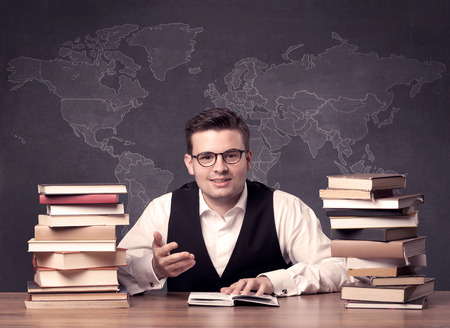 regional: A young ambitious geography teacher in glasses sitting at classroom desk with pile of books in front of world map drawing on blackboard, back to school concept.