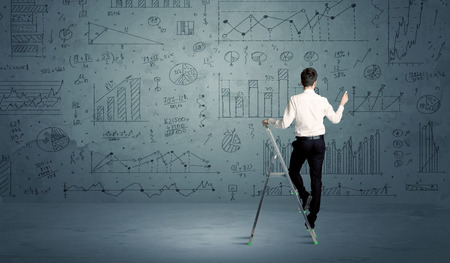 digitally: A businessman in modern stylish elegant suit standing on a small ladder and drawing pie and block charts on grey wall background with exponential progressing curves, lines, circles, angles, blocks, numbers Stock Photo