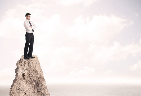 standing stone: Successful sales person with brief case standing on top of a mountain cliff edge looking above the landscape between the clouds
