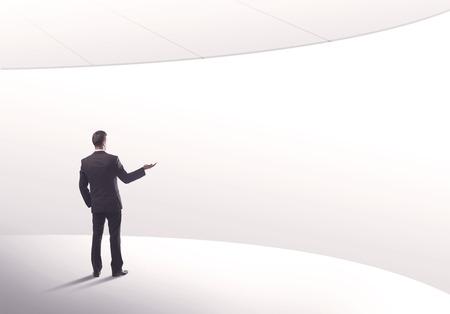 曲線の概念で空白領域のバック グラウンドで彼の背中にエレガントなスーツの若い販売事業者 写真素材