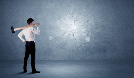 Business man hitting grungy wall with a hammer Stock Photo