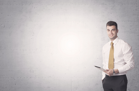 sales person: Young sales business person in elegant suit standing in front of clear empty grey wall background while talking on the phone