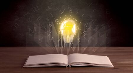 hovering: Shiny alphabet letters and yellow lightbulb hovering over open book Stock Photo